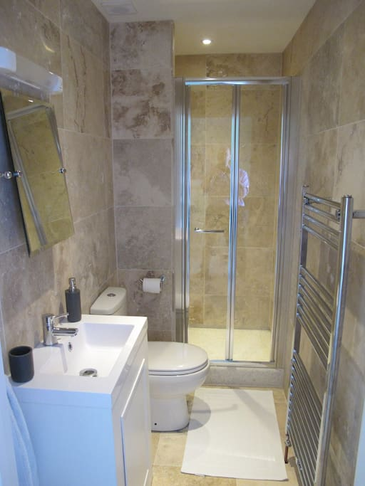 Modern shower room with stone tiled walls and floors.