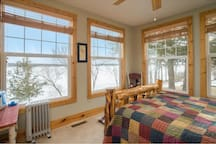 The Old Bear bedroom on main level.  5 giant windows to view lake.