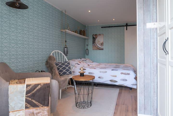 Een ruim ingericht gezellig kamer met badkamer