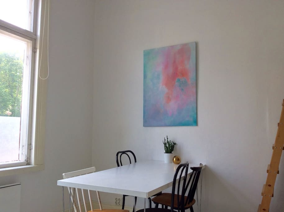 Dining table with space for four. The art made by the hosts gives color to the otherwise minimal color scheme.