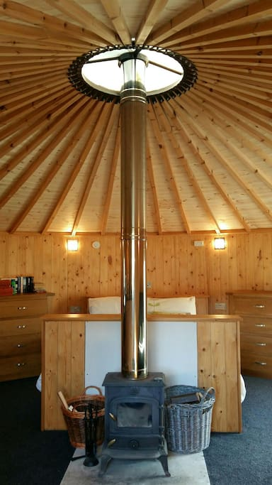 The calming space inside, all wood, showing the fire, storage  facilities and the bed!