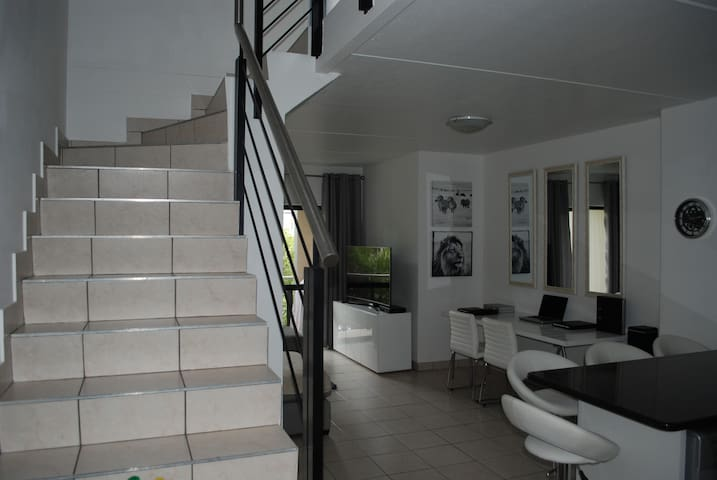 Entrance of the apartment and staircase leading up to two bedrooms and bathrooms