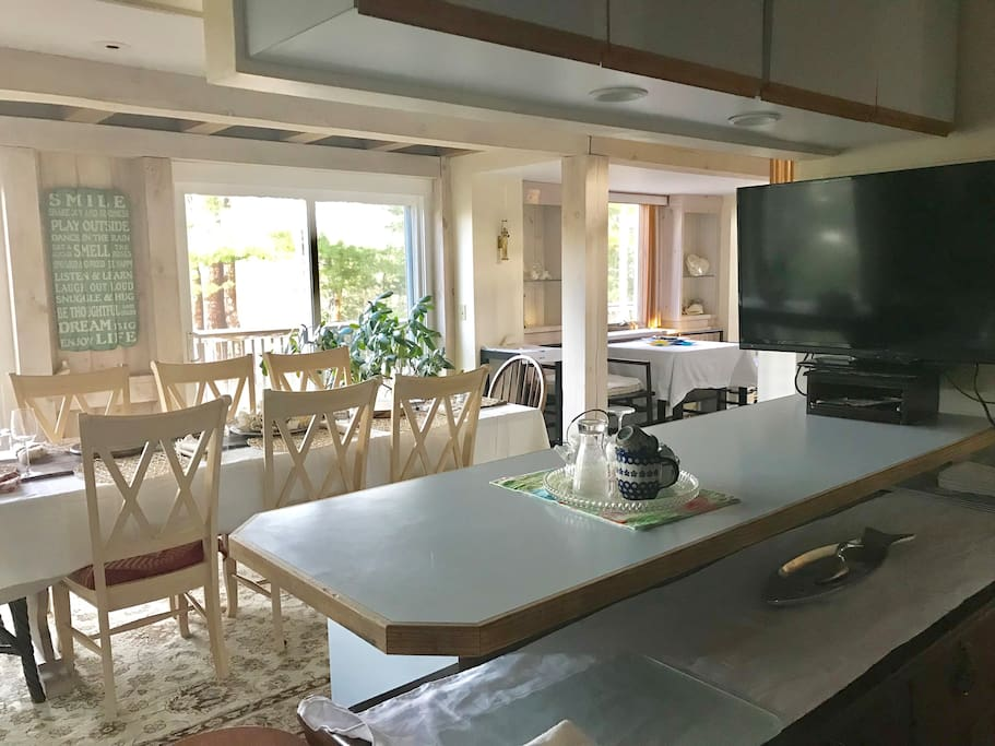 Open dinning room with TV and kitchen