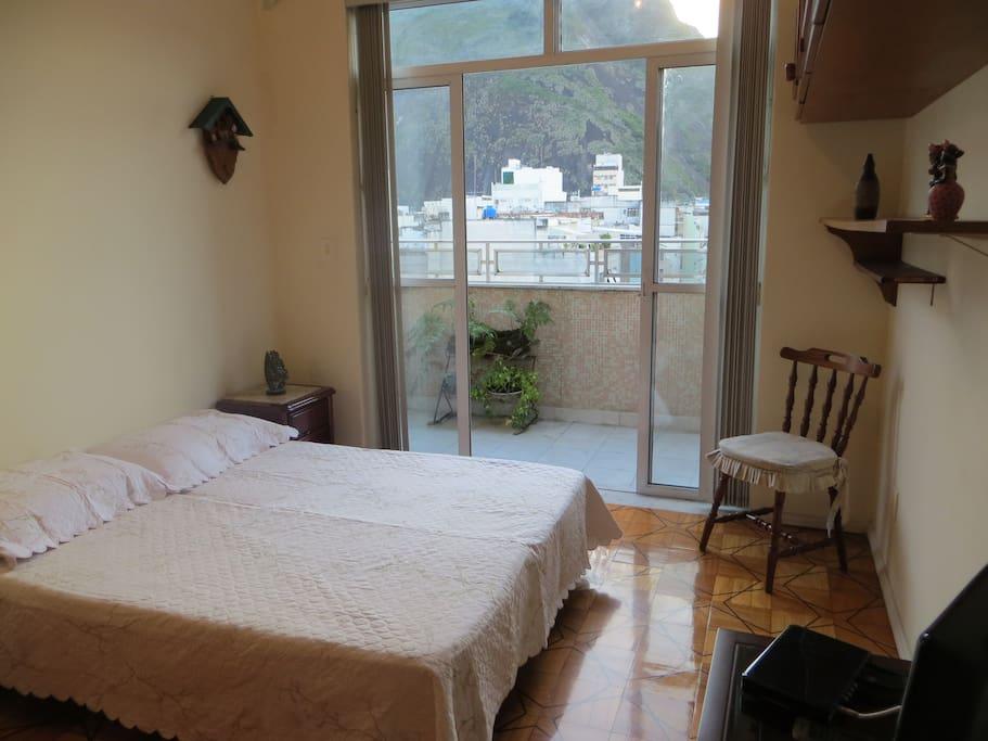 Configuração cama de casal. Quarto com varanda e vista para o Corcovado.  Bedroom with balcony and Christ the Redeemer view.