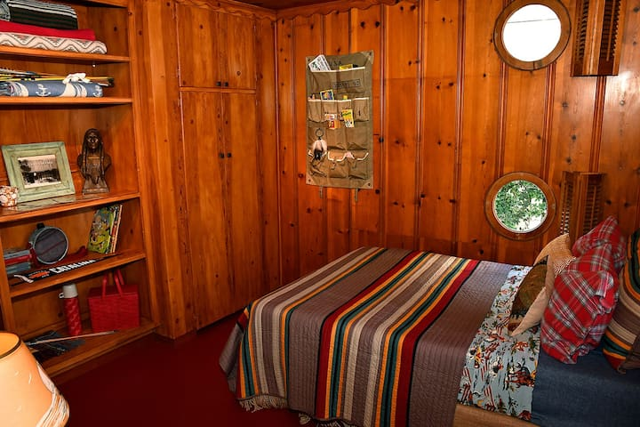 (# 3) front bedroom w/ two ship's porthole windows on side wall and a full-sized bed and large closet in back left corner