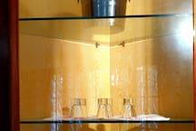 In sala da pranzo, nella vetrinetta: set da fonduta, bicchieri da vino flutes bicchierini da liquore e cestello da vino.  In the dining room, in the display case: fondue set, wine glasses flutes liqueur and grappa glasses and wine basket.
