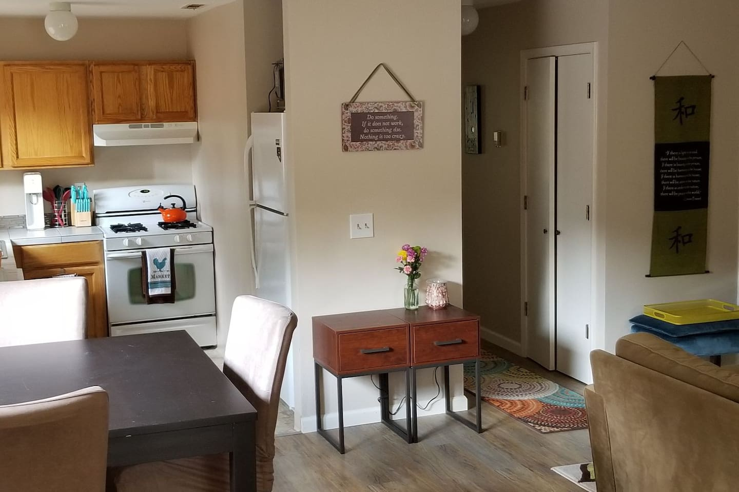 Fully equipped kitchen with gas stovetop; microwave on top of fridge; bar height dining table; stackable washer and dryer behind double doors in hallway.