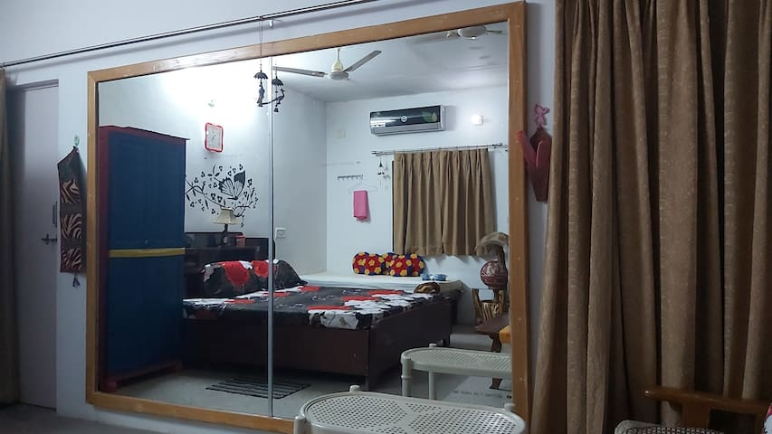 A big room provided with amenities like one double bed,one single bed ,big mirror,almirah, sofas .