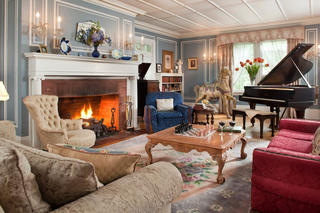 Cozy common room with grand piano and fireplace