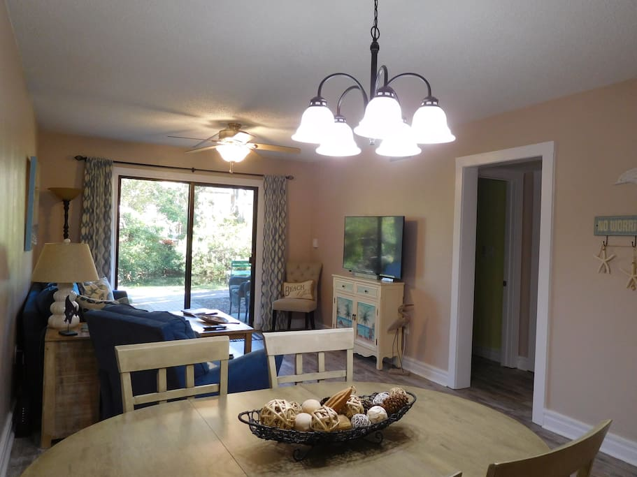 """Open living dining area with 50"""" smart TV, access to patio, pool and tennis courts"""
