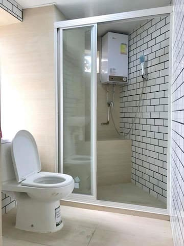 Decent bathroom with all necessities : Lavatory, toilet, shower.