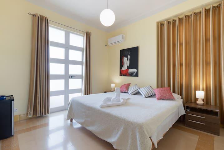 Esta es nuestra habitacion matrimonial, cuenta con una cama king size muy grande de 2*2mts, mucho espacio, puerta de acceso a la terraza exterior y una ventana, que garantizan una adecuada ventilacion. Climatizada  su baño privado.