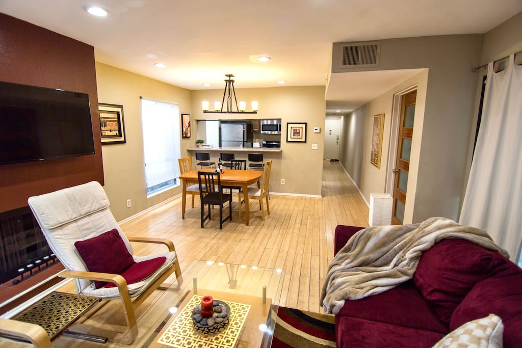 Living room with bamboo floors, sofabed, TV,  decorative fireplace, table with seating for 4-6