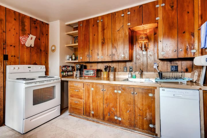 Fully equipped kitchen with dishwasher, oven, fridge, microwave, coffee maker, toaster.