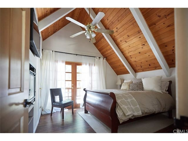 Top floor master bedroom with smart TV and electric fireplace. French doors lead to a private little deck overlooking the quiet cul de sac/forest settings!