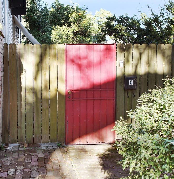 Red gate and lock box. Entrance to garden apartment and courtyard.