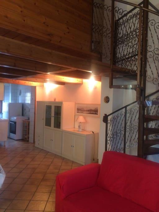 Vista dal soggiorno del mobile d'ingresso, della cucina e della scala a chiocciola che porta al soppalco.
