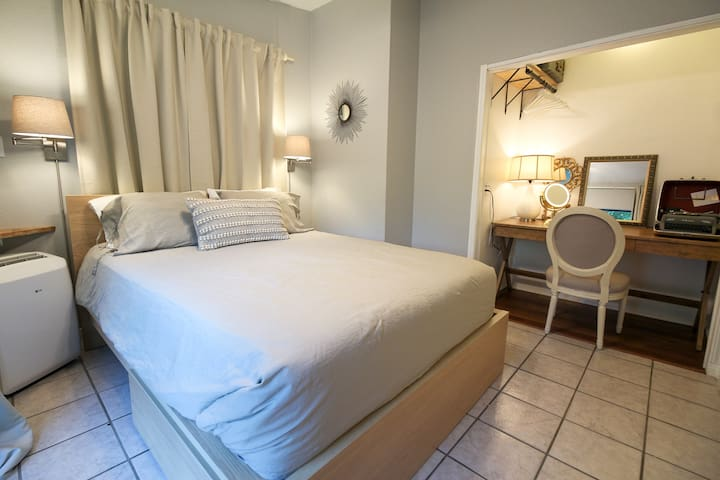 The bedroom features a queen bed with plenty of pillows and an ultra comfy mattress.