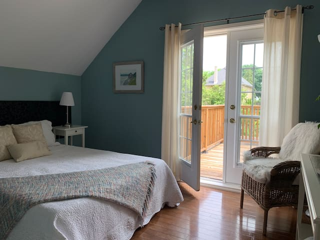 Light and airy bedroom with french doors opening onto an upper deck.