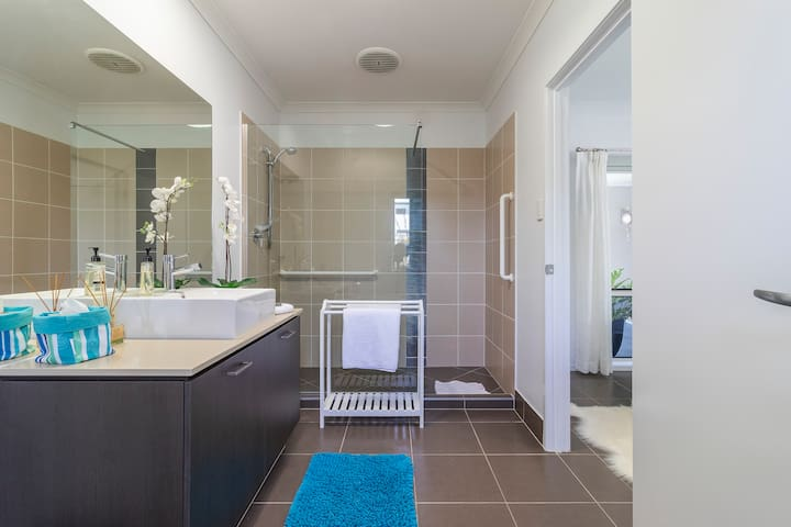 The large walk in shower has mobility assistance rails available, with a small lip to shower access and 66cm clearance between wall and shower panel.