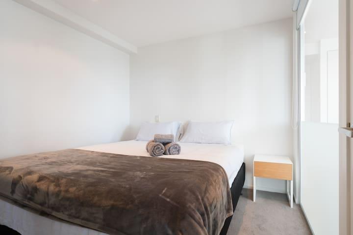 Bedroom 2, Queen bed, Wardrobe, Black-out blinds, Nightstand, En-suite bathroom.