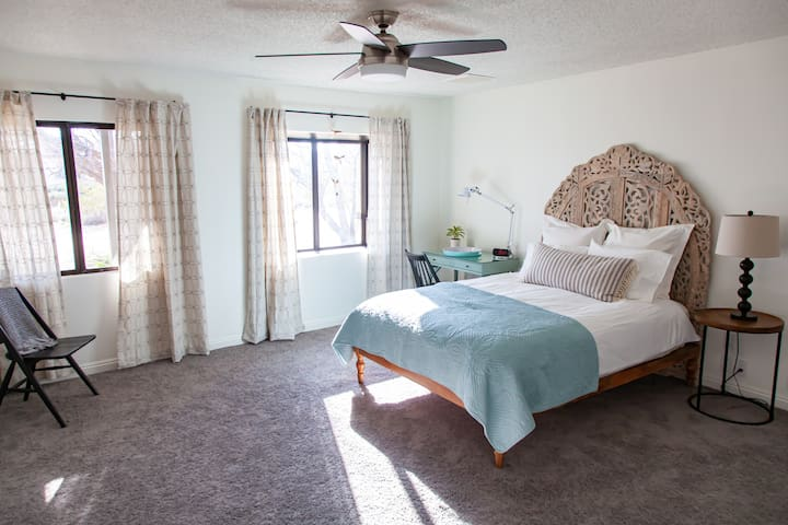 Spacious master bedroom has a large walk-in closet, overhead fan, and adjacent bathroom equipped with a combined tub/shower.