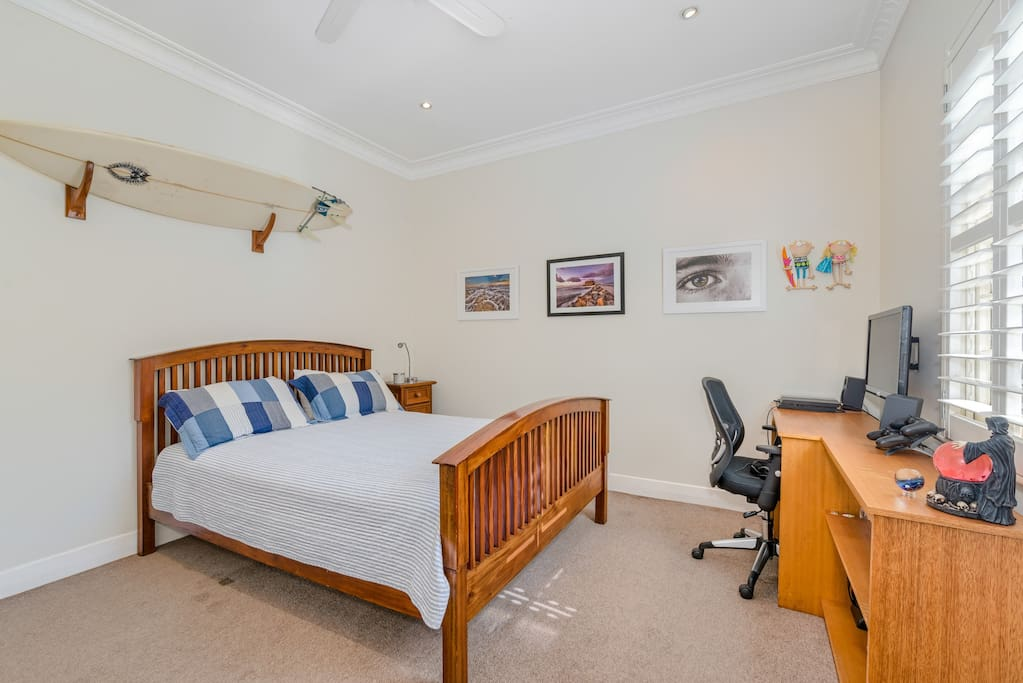 Room with queen bed and work desk