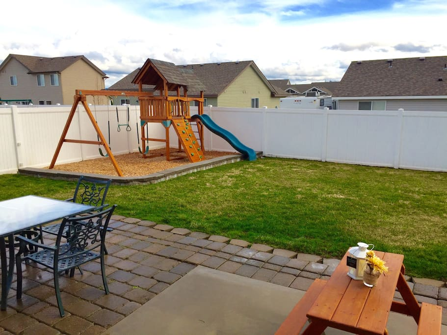 Fully fenced backyard with BBQ, Playset, and dining table.