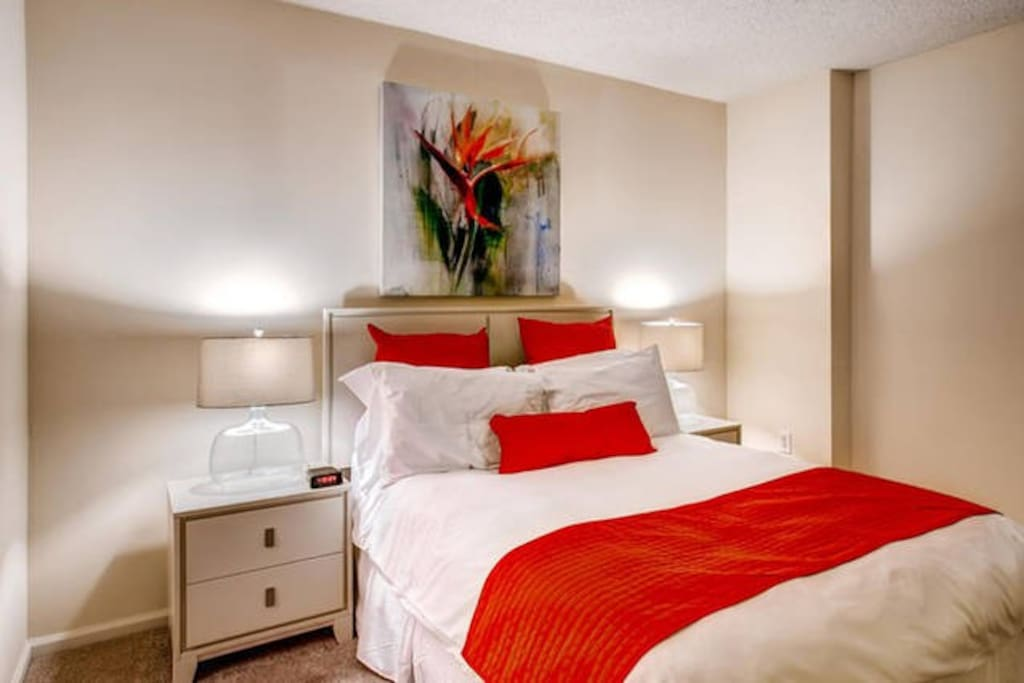 The bedroom features a deluxe queen size bed with our indulgent custom linens, fluffy duvet, and plush pillows