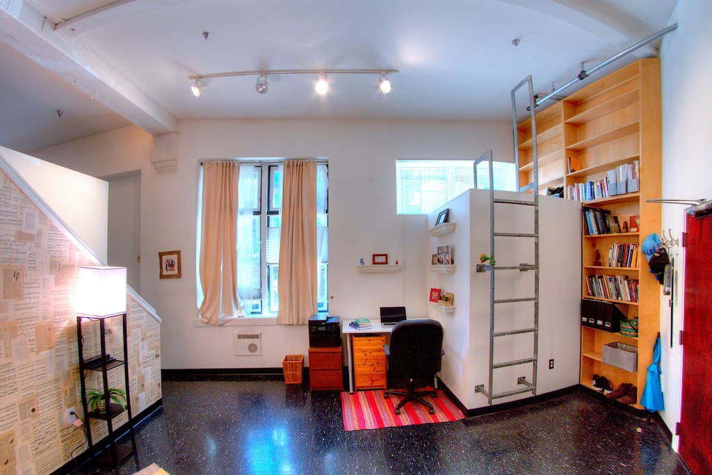 A writing desk beneath the built-in library and reading nook.