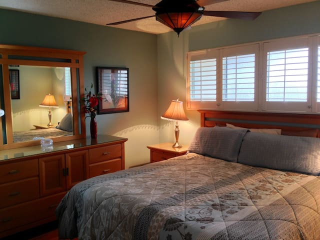 The bedroom, featuring a comfortable king size bed, full set of dresser drawers with glass-top and vanity mirror, and overhead fan. The bedroom also has a closet space and an additional fan for your comfort.