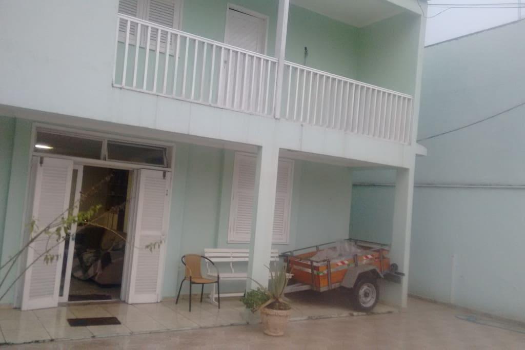 Parte frontal externa da casa, varanda e garagem.