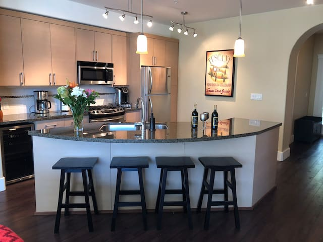 Spacious gourmet kitchen with granite counter tops, stainless steel appliances, breakfast bar, wine fridge and gas range.