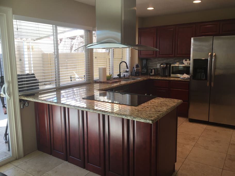 Fully stocked kitchen with newer appliances and granite countertops. Pass through to outside bar