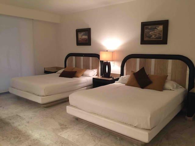 Dos camas matrimoniales con Televisión y ventilador.