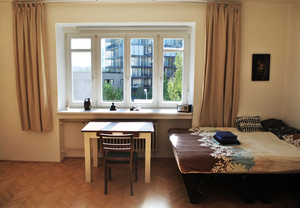 Big and spacious room with a bed, working table with a chair, wardrobe, cupboards and dress stand.