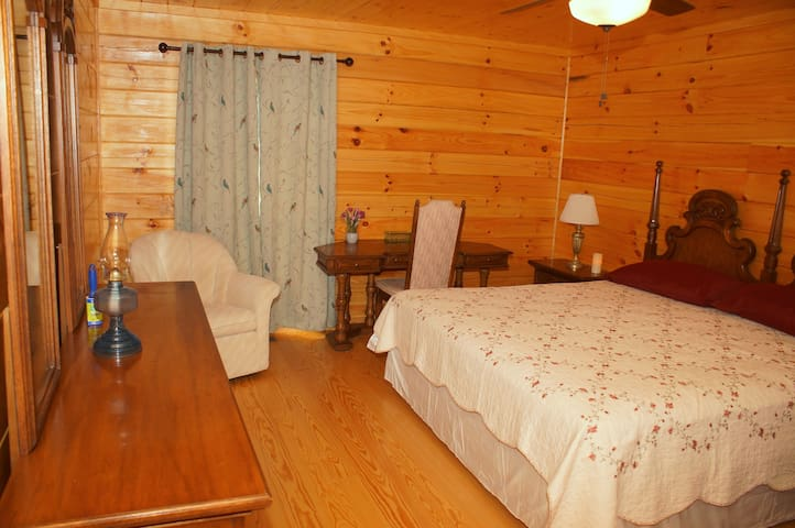 King bedroom with writing table, wardrobe, dresser, and private bathroom; 1st floor.