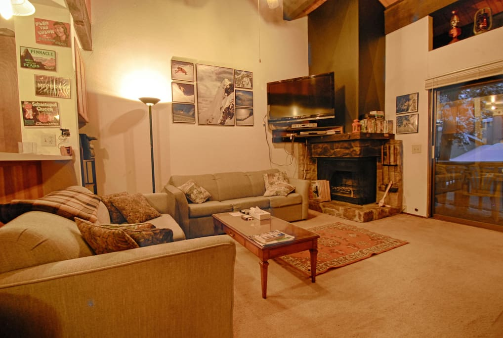 Living area with sleeper sofa, wood burning fireplace, deck and flat screen TV