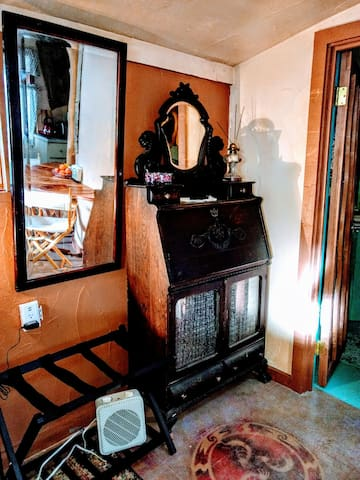 Full mirror and luggage rack. Also, outlets at bedside have USB ports for your electronics. Antique secretary folds down to another workspace.