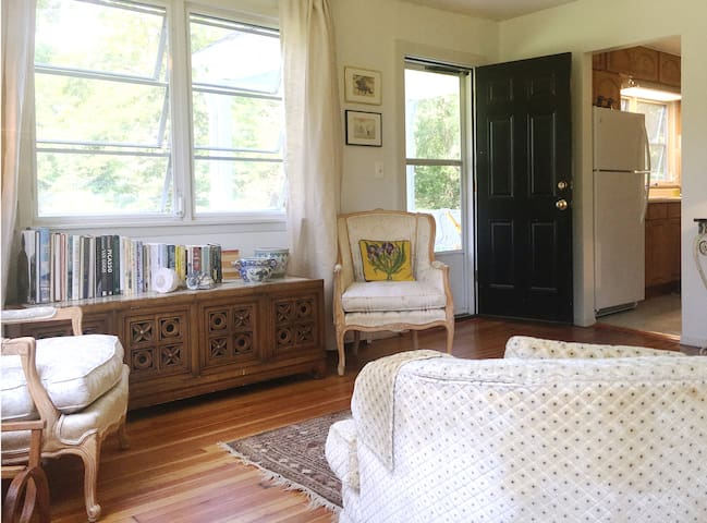 Living Room with main entrance. Windows facing pond and orchard, stocked with art books, classical and contemporary fiction, games and puzzles.