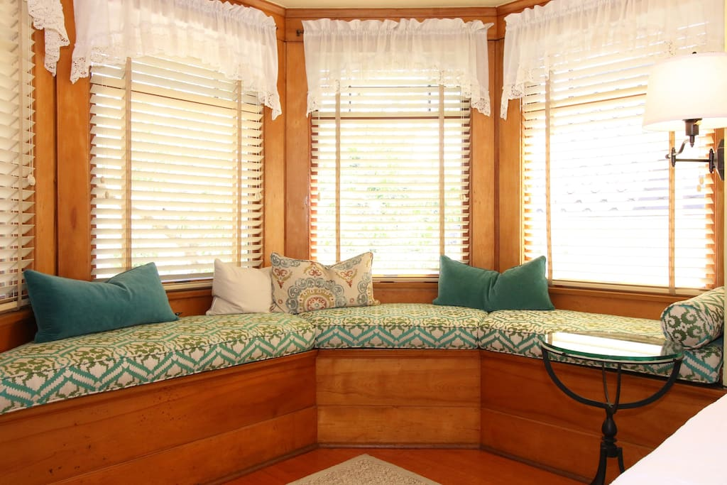 A beautiful window seat with lots of light streaming in through the windows