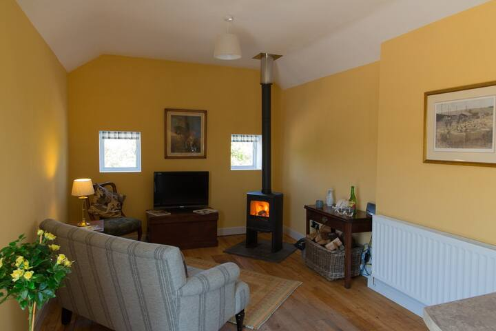 Comfortable sitting room with kitchen and breakfast bar. Wood burner for those winter nights. Eco paints and insulation.