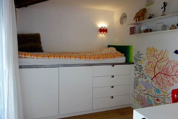 Bedroom 3, one elevated adult size single bed, 90x200 cm, built-in cupboards and shelves