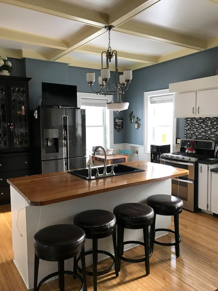 Kitchen with full butcher block and gas stove and dual ovens