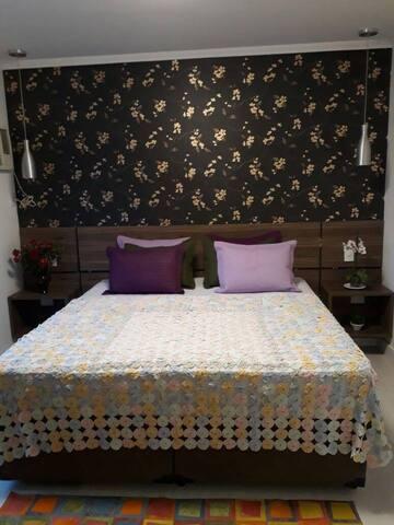 Quarto 02 - Suíte confortável com cama king. Quarto avarandado com janela antirruído e ar condicionado.