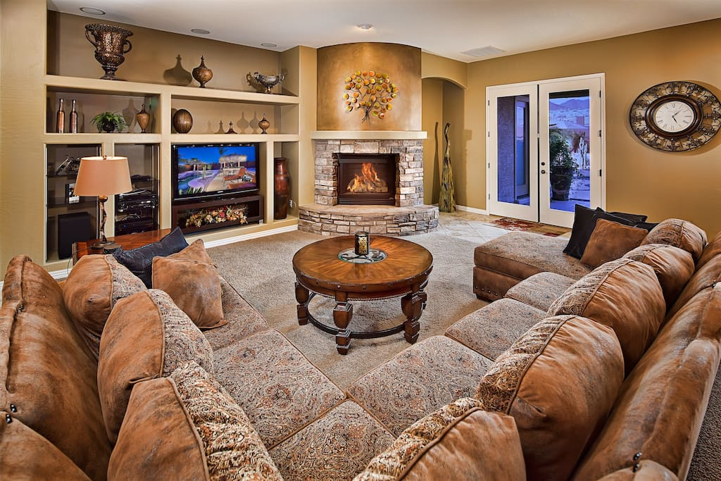 Beautiful living room with high ceilings, fireplace, and large HD TV.