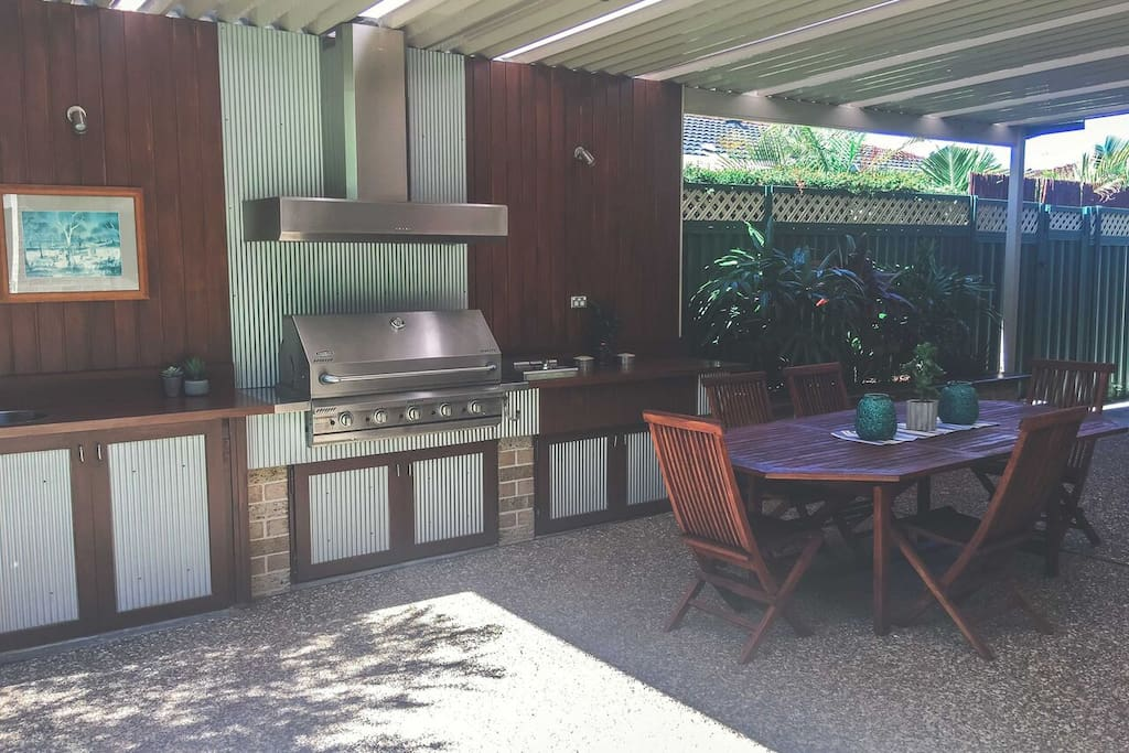 huge covered outdoor built-in bbq area with seating for 8, small bar fridge and sink.