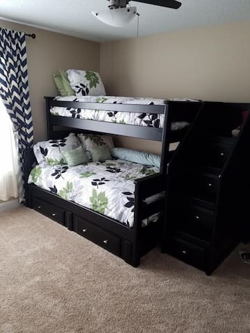 Full size bunk bed with twin bunk above. Closet space and dedicated workspace.