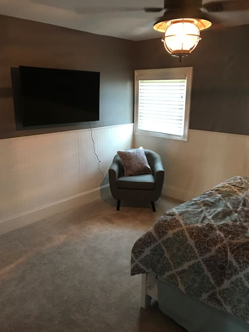 Mounted TV and chair in bedroom 1