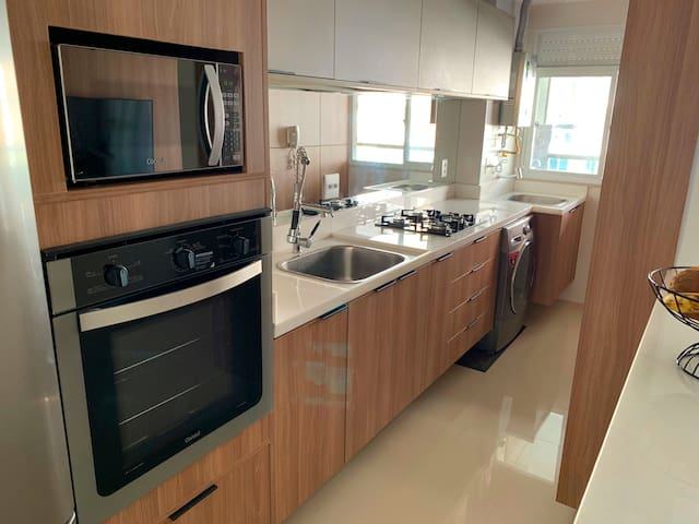 Fully equipped kitchen includes all new appliances, two sinks, microwave, stove, oven and washer-dryer.